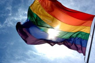 Rainbow_flag_and_blue_skies