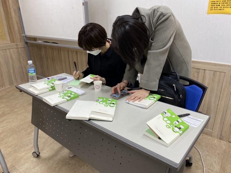 월례회가 끝나고 김소영 작가가 테이블에 앉아 '어린이라는 세계' 저서에 사인을 하고 있다. 김소영 작가 왼편으로는 사인 받으려는 사람이 서있다. 테이블엔 대여섯권의 책이 널려 있다.