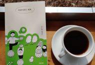 테이블 위 왼쪽 편에 '어린이라는 세계' 책이 놓여져 있고 오른편엔 커핏잔과 잔받침이 놓여 있다.