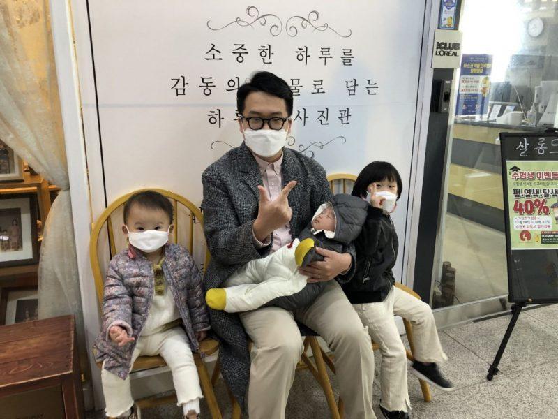 서성민 변호사가 셋째 자녀를 품에 앉고 엄지와 검지로 브이표시를 한채 의자에 앉아 있다. 양 옆에는 첫째, 둘째 자녀가 앉아 있다.