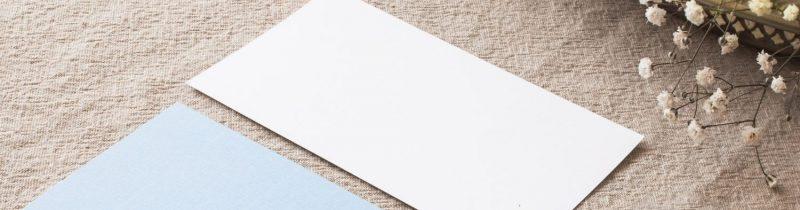 베이지색 테이블보 위로 하늘색, 흰색의 무지 엽서가 놓여있따