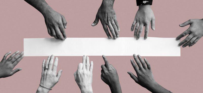 다양한 피부색을 가진 손들이 흰색 종이에 손을 뻗고 있다